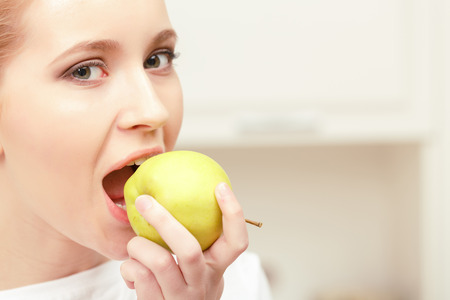 going for it: Desire for vitamins. Close-up of a young lady holding green apple in her hand near her face and going to bite it