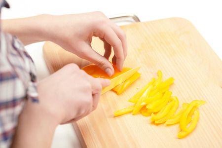 Bright and delicious. Manicured hands of a young lady cutting bright yellow pepper in thin slices on the table