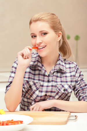 fresh taste: Fresh taste. Blonde young woman biting and tasting a small slice of red pepper standing near the table Stock Photo