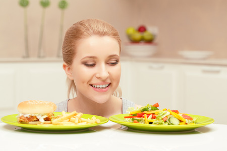 eat right: Made right choice. Close-up of a smiling lady who decided to eat vegetables but not fast-food looking at plate with salad