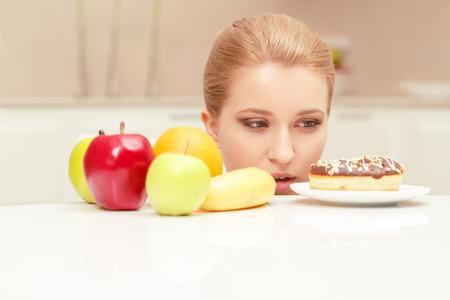 Resistir la tentación. Dudando joven señora agradable mirando buñuelo en su mesa, pero sintiéndose inseguro acerca de comer o comer plátano, naranja y manzana Foto de archivo