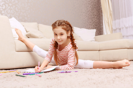 lie forward: Comfy in any case. Little nice girl drawing with splitting legs apart Stock Photo