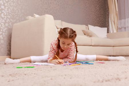 legs apart: Studing through gymnastic. Cute little girl drawing with splitting legs apart.