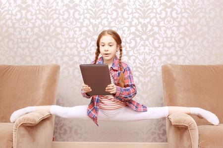 legs apart: Surprise. Little surprised girl splitting legs apart between sofas