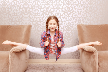 legs apart: Feel wonderful. little flexible girl splitting legs apart and showing that everything is cool.