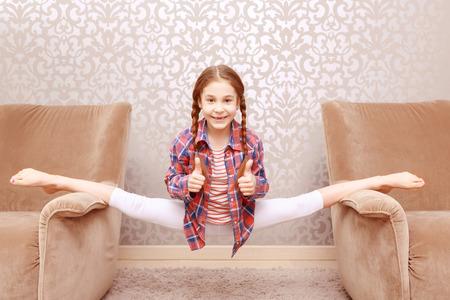jambes �cart�es: Se sentir belle. petites jambes flexibles de fractionnement de fille et montrent part que tout est cool. Banque d'images