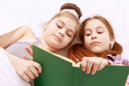 In any pose. Pair of little girls reading book in green cover with great interest Stock Photo