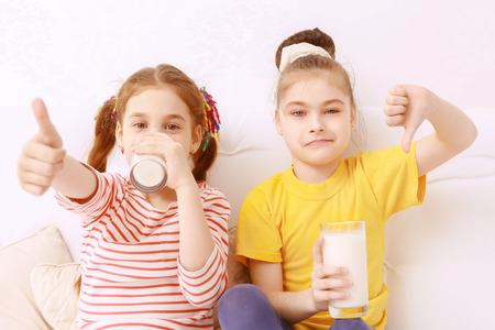 judging: Tastes are different. Two cute kids drinking milk and  judging it
