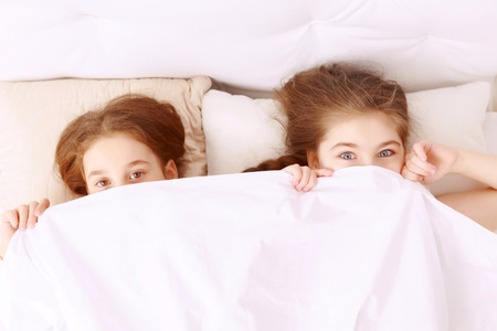 hilarious: Hiding from you. Little two hilarious girls lying on bed covered with white blanket.