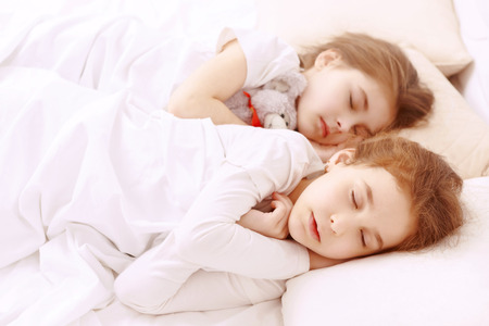 next to each other: Fast asleep. Two little cute girls lying next to each other on white bed and sleeping.