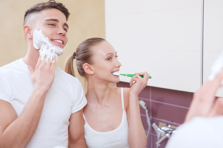 morning routine: Everything together. Lovely pair doing morning routine together in front of mirror in bathroom. Stock Photo