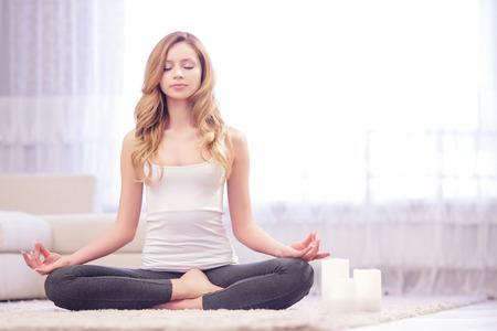 プロセスを楽しんでいます。白いキャンドルは、目を閉じてカーペットの上に座って近く瞑想穏やかな女性で蓮をもたらします。
