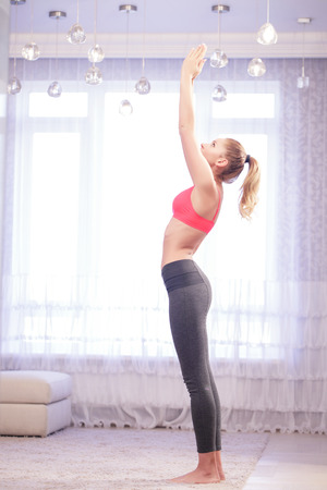 salutation: Greet sun. Young pretty lady standing and doing sun salutation yoga pose indoors.