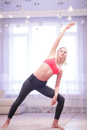 keep fit: Keep fit. Pretty young lady doing stretching at home in white decorated living room. Stock Photo