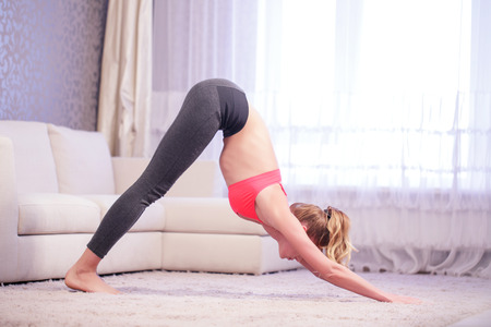 leaning forward: Awake sense. Young woman leaning forward in yoga pose indoors in white decorated living room.