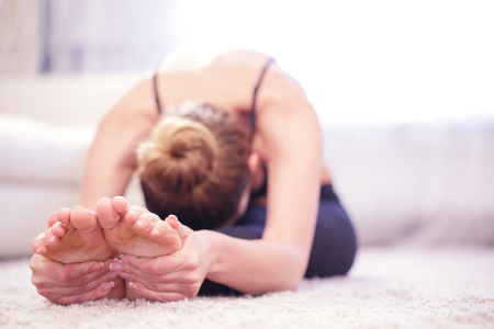 leaning forward: Stretch out. Young woman doing stretching exercises by leaning forward her body to her legs. Stock Photo