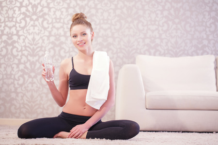 satisfying: Satisfying thirst. Young pleasant woman having rest after sport exercises by sitting in lotus pose and holding bottle of water and white towel.