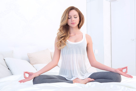 yoga pillows: Inner harmony. Young beautiful woman sitting on her bed in bedroom and meditating.