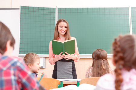 Young teacher. Young pleasant women teaching at school in junior school. Stock Photo