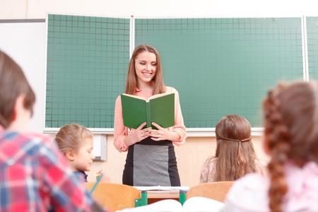 junior student: Young teacher. Young pleasant women teaching at school in junior school. Stock Photo