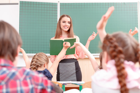 Be first. Little pupils raising their hands during classes and teacher explaining new material. Stock Photo