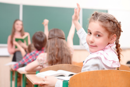 half turn: Look at me. Pupil raising hand turned away from teacher in classroom. Stock Photo