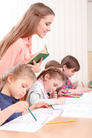 excellent work: Excellent work. Young teacher standing with book and checking work of pupils. Stock Photo