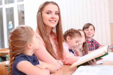 teacher: Time to read. Young smiling teacher sitting at desk near pupils, holding book and reading to them