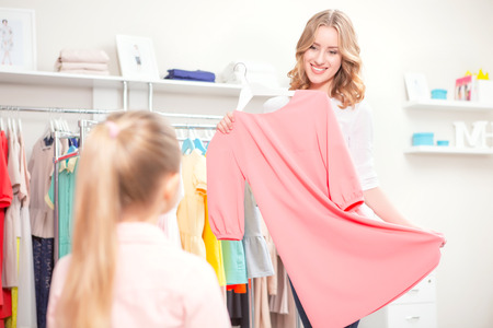 waist up: Happy shopping. Young mother showing a pastel pink dress to her small daughter standing back in a boutique waist up selective focus