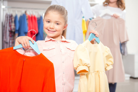 chose: What to chose. Small girl standing in a fashion store holding hangers with red and yellow dresses, her mother standing behind