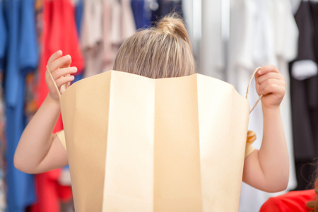 curiously: Small girl looking curiously inside a package with new clothes in a fashion store Stock Photo
