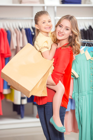 spending full: Shopping. Young mother standing in a fashion store holding her daughter with packages both smiling