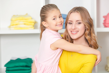 spending full: Happy mother holding her smiling daughter in a fashion store, shelves with bright clothes behind