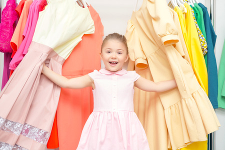 spending full: : Portrait of a small joyful girl standing between racks with colorful dresses and touching them in a fashion store Stock Photo