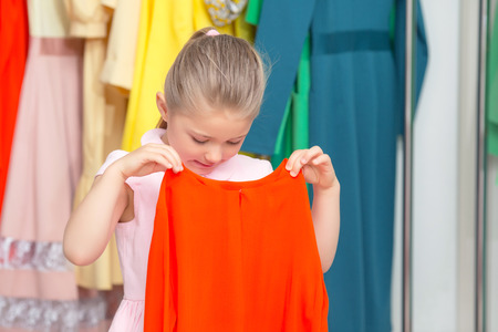 fitting in: What a color. Small girl fitting a red dress in a fashion store