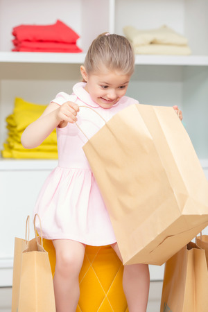 look inside: Look inside. Small happy girl looking inside her package with a new dress in a fashion store Stock Photo