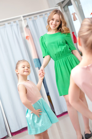 full length mirror: Young mother standing and holding the hand of her daughter while looking in the mirror in a fashion store
