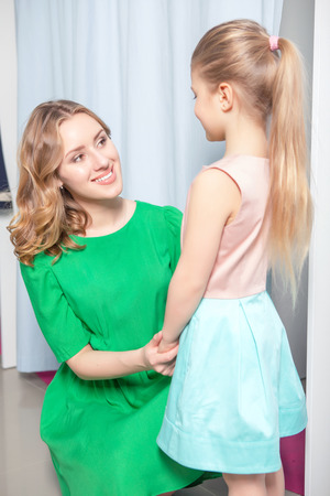 fitting room: Young mother looking proudly at her beautiful small daughter in a fitting room Stock Photo