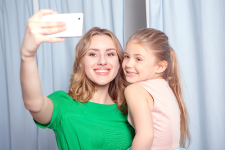 fitting room: Selfie time. Young woman making selfie in a fitting room with her smiling daughter