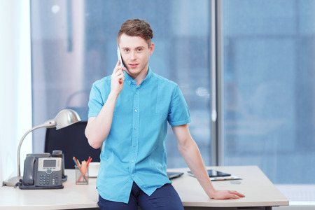 youthful: Serious conversation. Youthful businessman sitting on desk covered with office equipment and seriously talking per mobile phone. Stock Photo