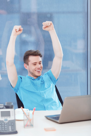 arms above head: It is victory. Ceerful businessman sitting at desk covered with office equipment with arms above his head and is glad of his success. Stock Photo