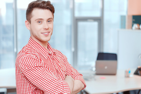 youthful: Be confident. Youthful smiling office worker standing with crossed arms.