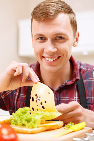 say cheese: Say cheese. Handsome smiling man adding cheese to sandwich.