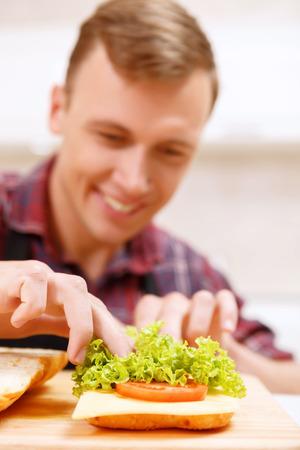 � fond: Faire fond. Close up de sourire jeune homme pain d�corer de feuilles de laitue