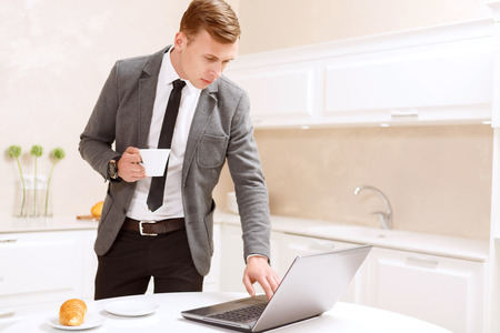 Concentrated on work. Serious handsome businessman standing with cup of coffee and using computer in white decorated kitchen. photo