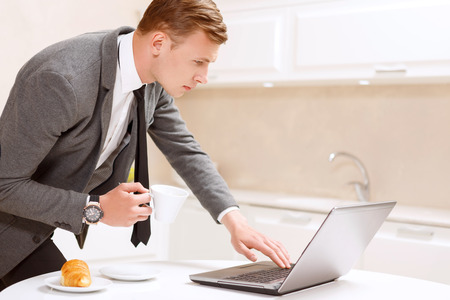 Checking news. Businessman is leaning above computer and holding with cup of coffee in white decorated kitchen. photo