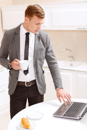 Before leaving. Concentated businessman standing with cup of coffee and using computer in white decorated kitchen. photo