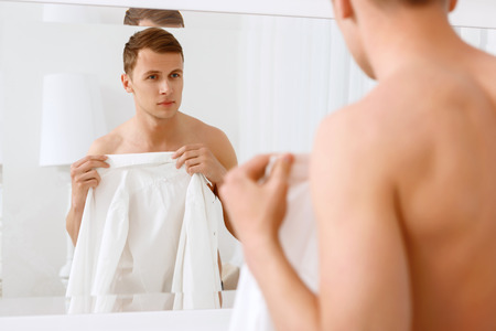 half nude: Feeling of safety. Young handsome man standing in front of mirror and covering himself with white shirt