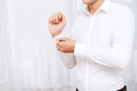 Last step. Close up of man buttoning up sleeve of white shirt on background of white curtains.