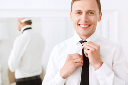 finishing touches: Finishing touches. Young smiling man fixing his tie on background of mirror.
